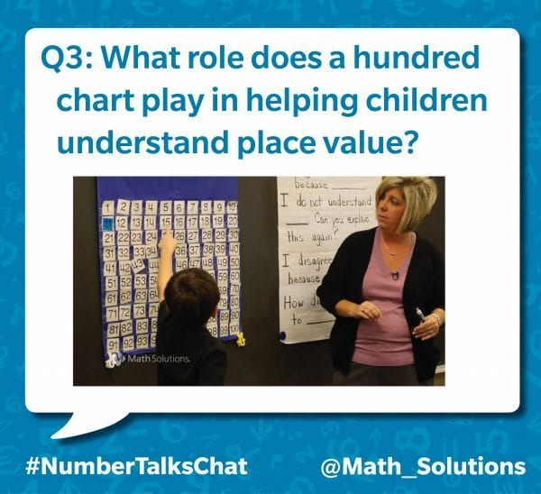 student pointing at the number 15 in a grid of numbers. a teacher stands nearby | q3: what role does a hundred chart play in helping children understand place value? #numbertalkschat @math_solutions