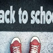 a child's sneakers appear with a concrete background and a sign that reads back-to-school | back-to-school