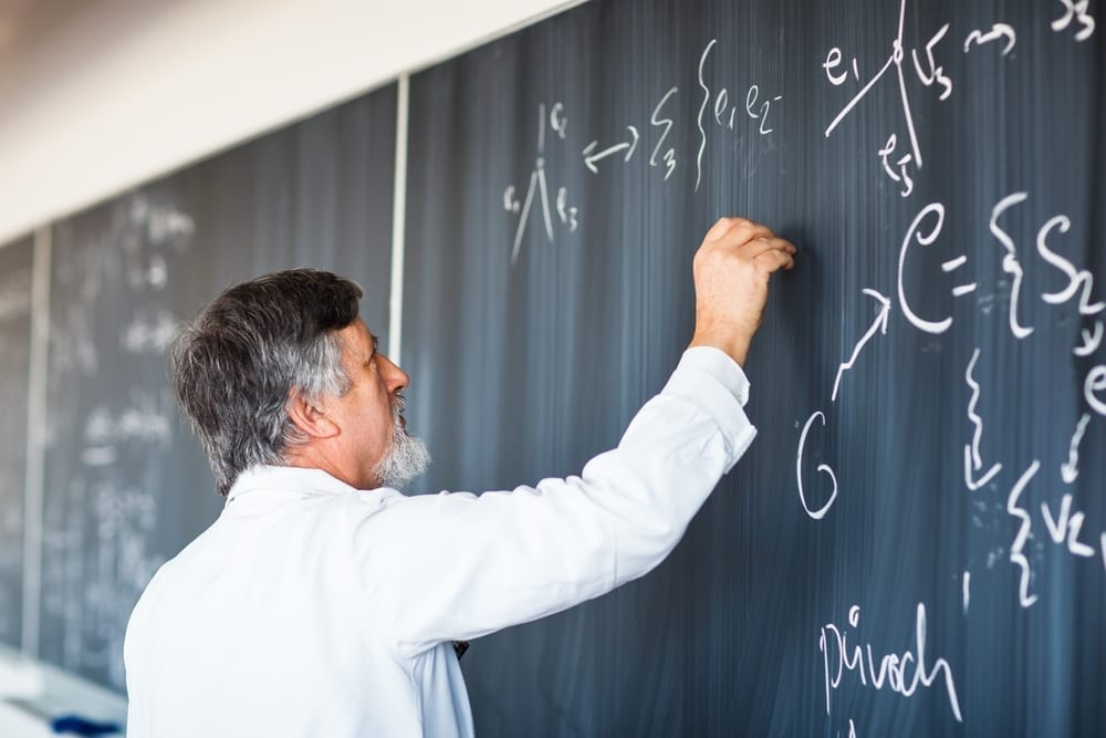 bearded teacher writing on chalkboard