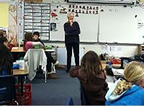 Image of Marilyn Burns, founder of Math Solutions, standing in a classroom with students, leading a lesson
