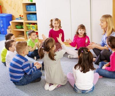 Preschool: Young smiling teacher singing with group of children. Learning and having fun.