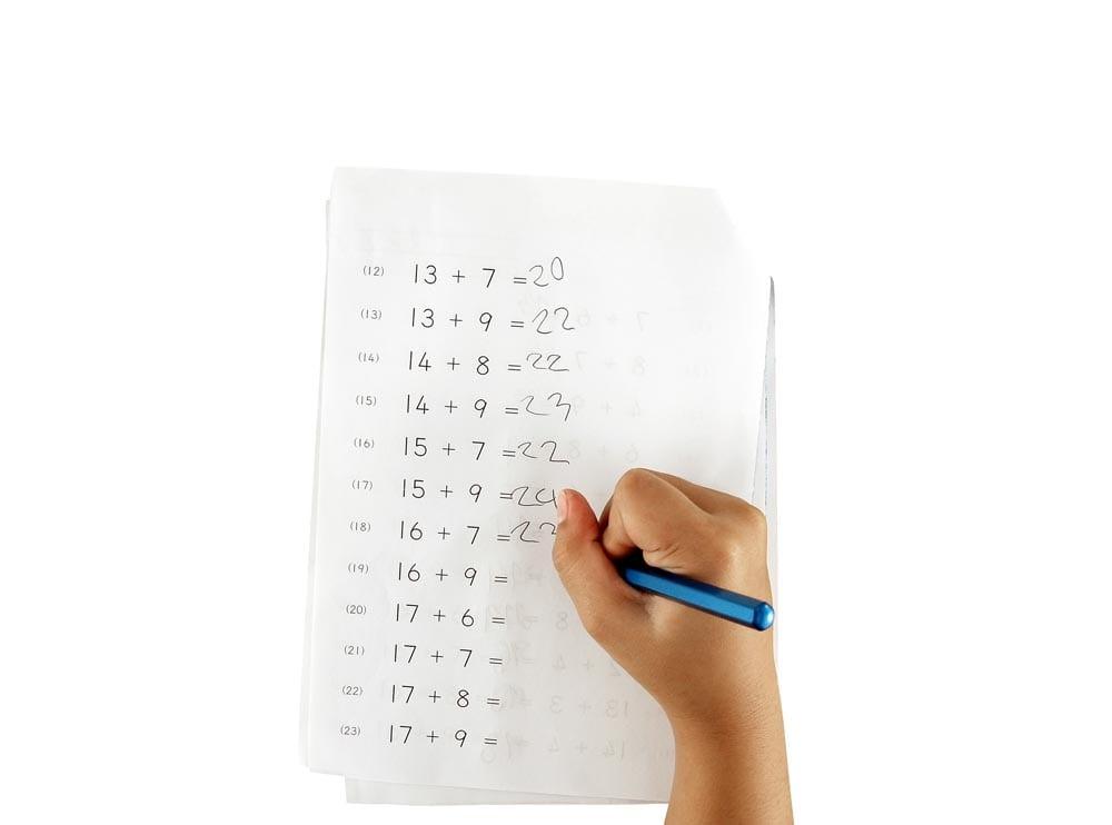 hand of little girl doing maths homework isolated on white
