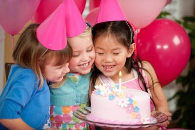 Children at a birthday party with a cake.