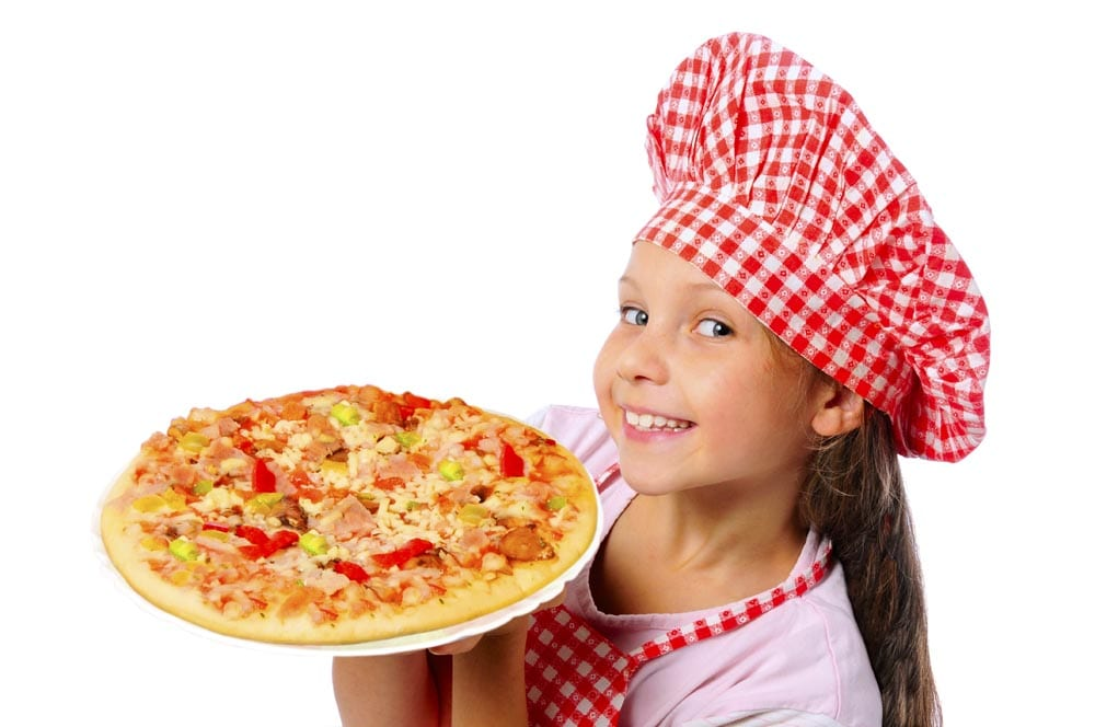 Young girl in a chef hat smiling and holding a pizza