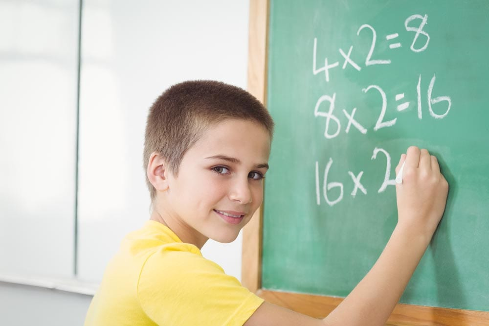 Smiling pupil calculating on chalkboard in a classroom
