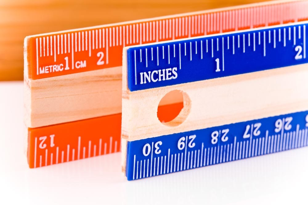 Units of measurement for length: inches (the English system) and centimeters (the Metric system). Rulers are aligned so the left edge of the ruler in the foreground marks the conversion of one inch into centimeters (roughly 2.5cm).Shot at f/13. Most but not all imperfections cloned out of rulers.