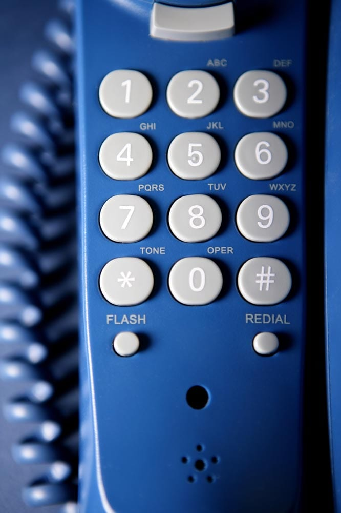 Close-up of a landline telephone keypad. Blue tones, shallow depth of field.