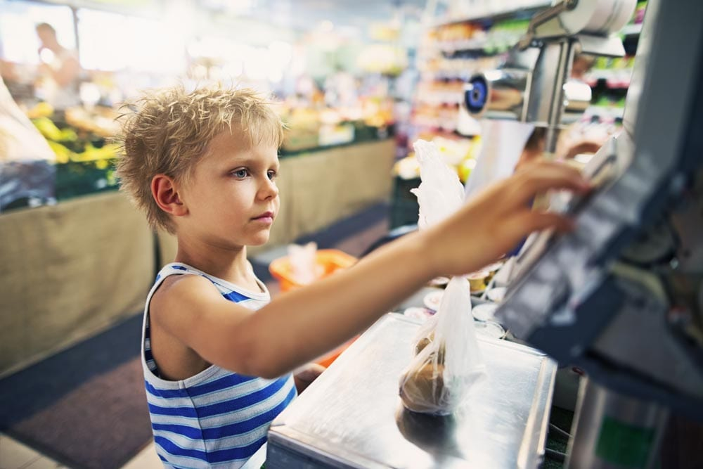 Little boy aged 7 is weighing groceries at a supermarket store scales.