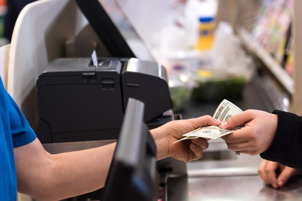 Woman giving cash when paying at a supermarket