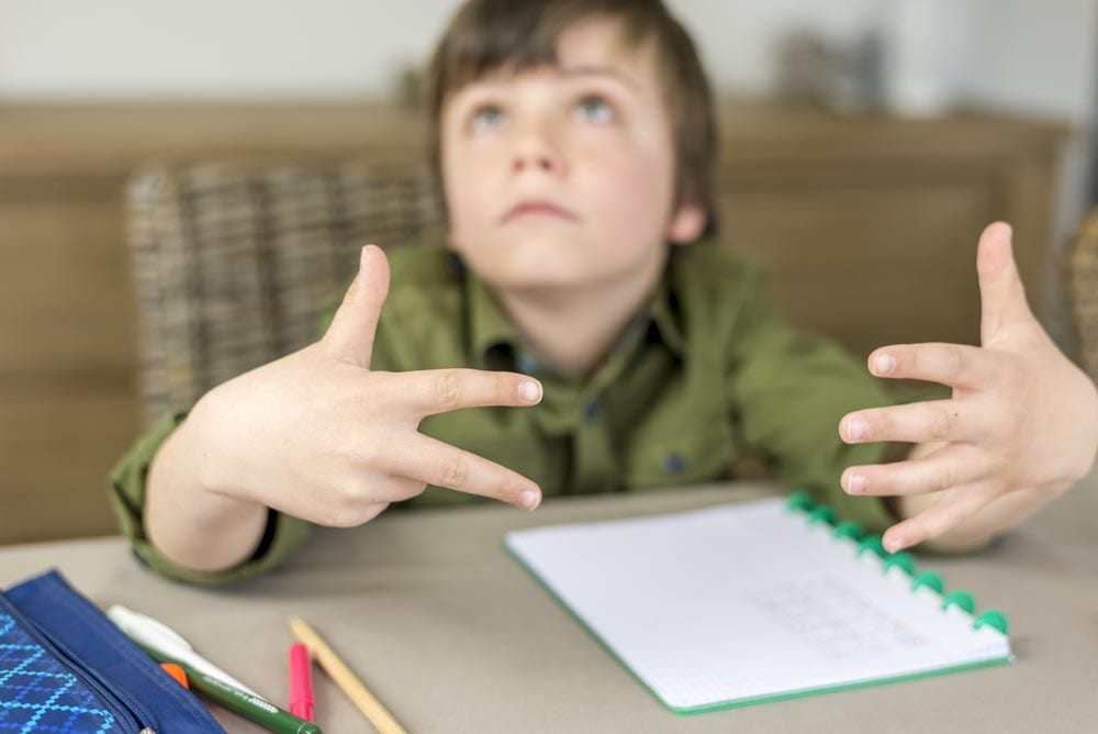 boy doing homework, counting on his fingers. shallow depth of field