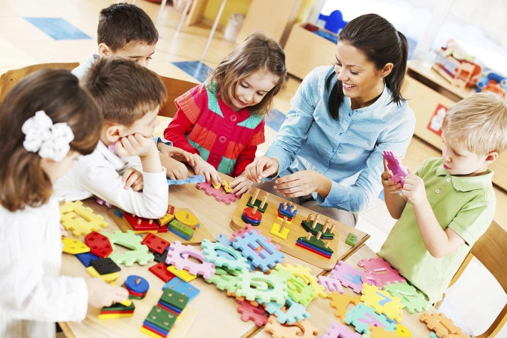 Group of kids playing together with their young nursery teacher.