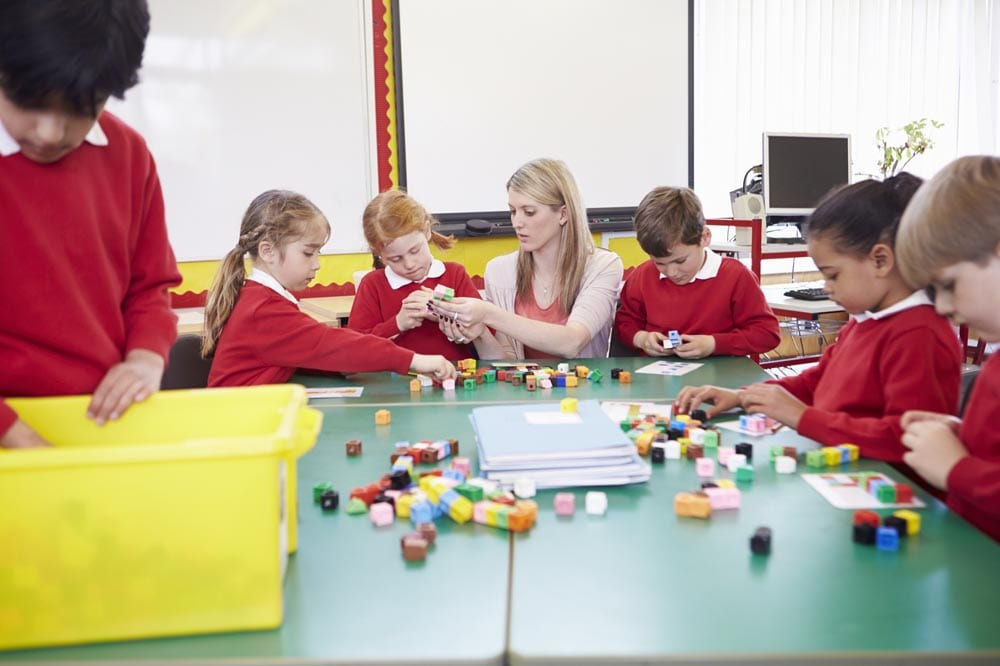Primary School Pupils And Teacher Working With Coloured Blocks