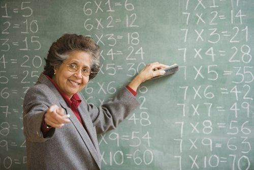 older teacher in front of chalkbaord with math problems smiling and pointing at camera