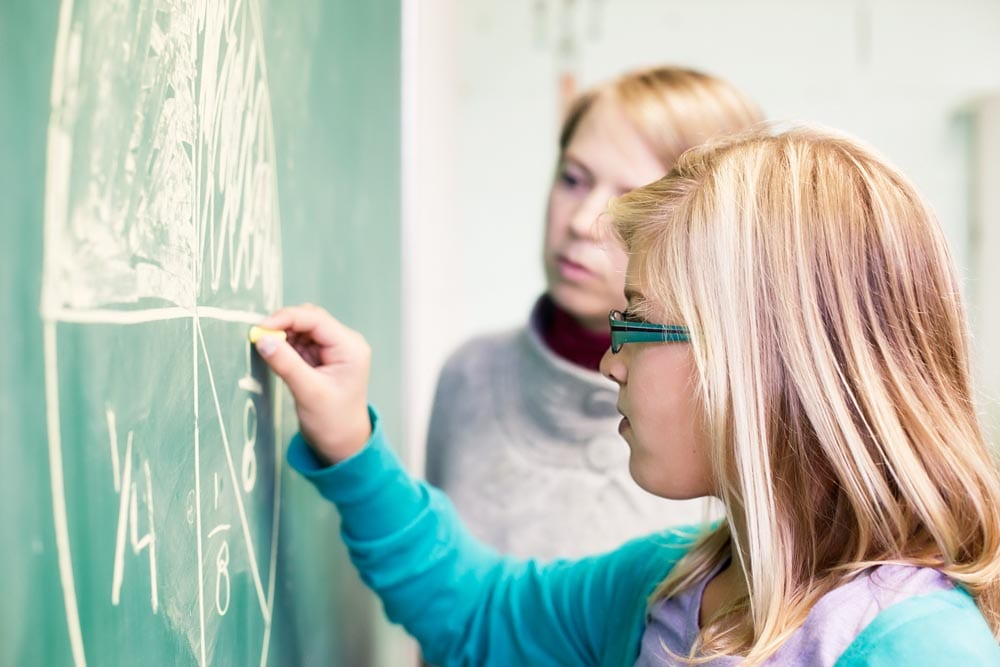 Preteen girl learning fraction by drawing a pie on the chalk board under the supervision of her teacher.