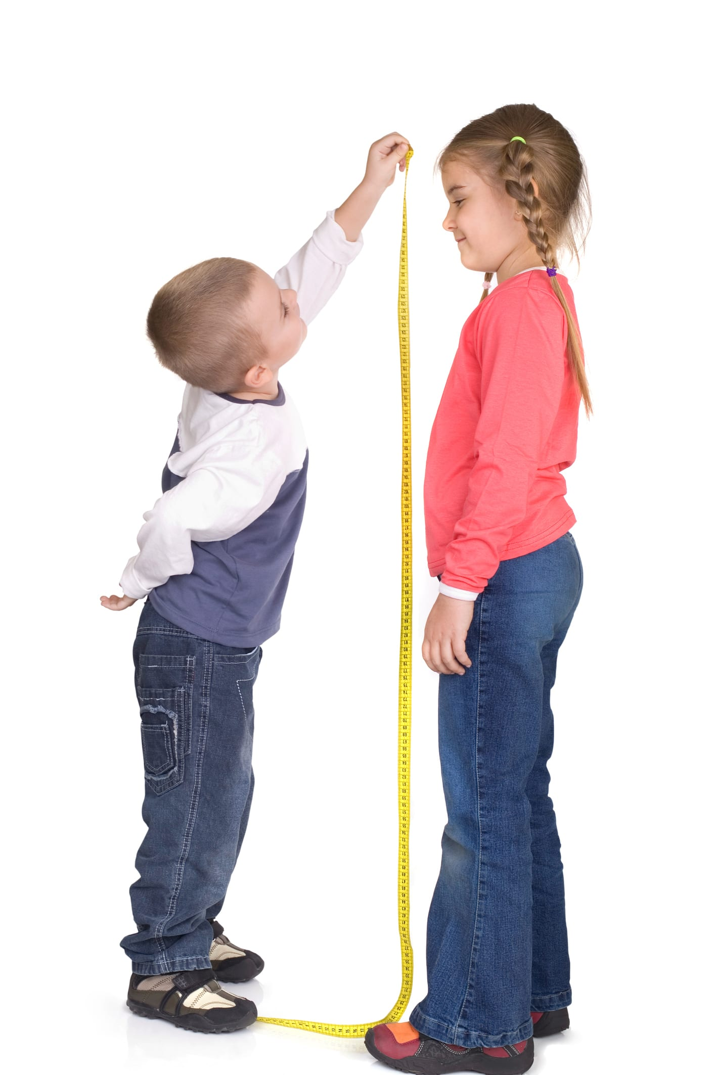 Little boy measuring the height of a slightly taller girl.