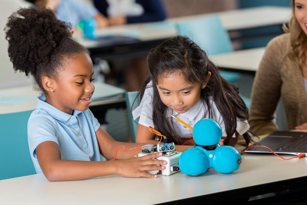 Diverse elementary schoolgirls enjoy building a robot in technology class at STEM school. A Caucasian teacher is helping them. They are wearing school uniforms.
