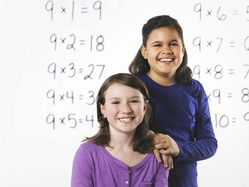 two middle school aged years, both smiling, one sitting and one standing in front of a whiteboard with multiplication tables on it | Math Solutions