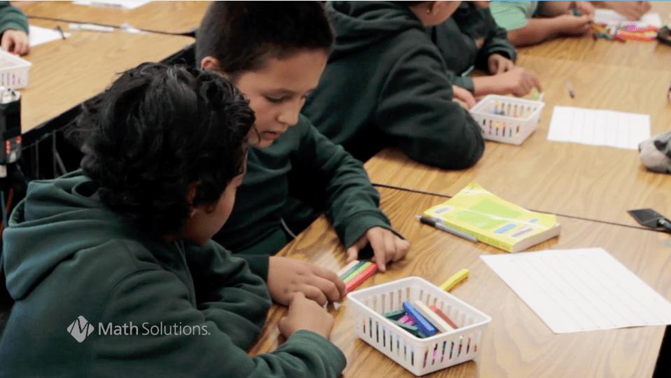 2 children in green school sweatshirts working with cuisenaire rods
