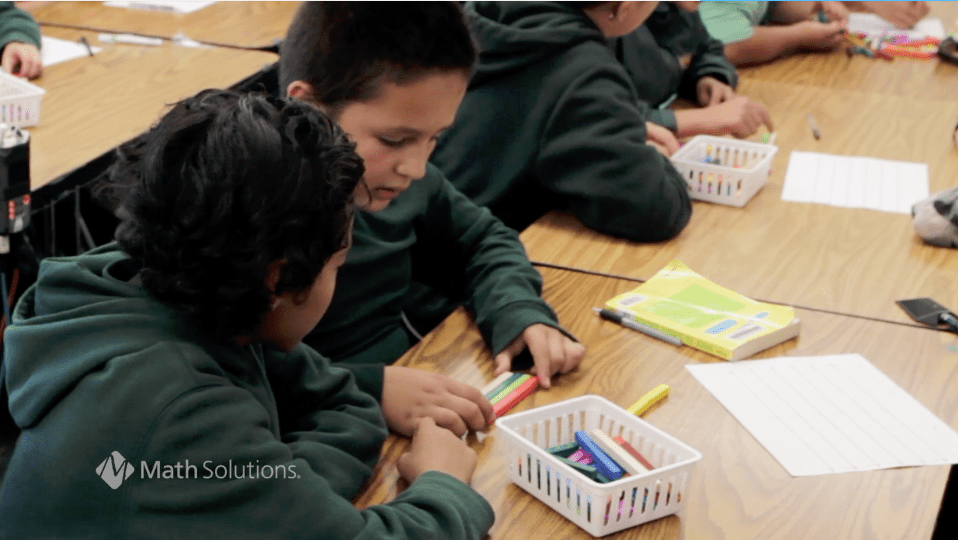 2 children in green school sweatshirts working with cuisenaire rods