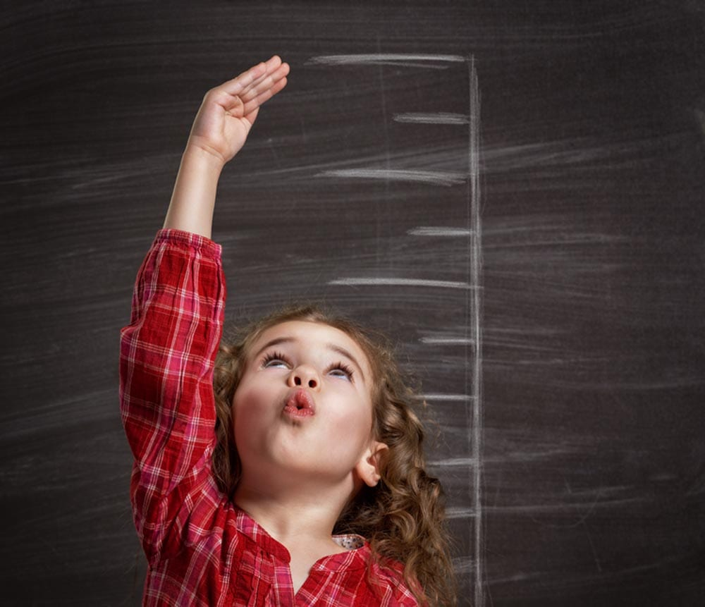 Young girl standing in front of a blackboard estimating her heigth
