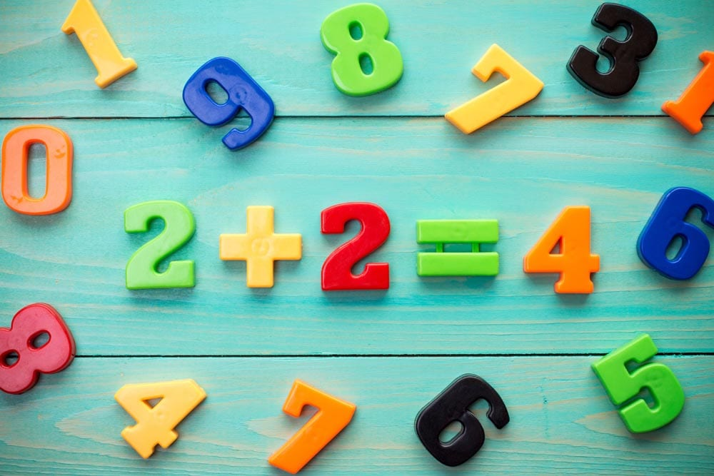 Math example with numbers magnets on a blue wood background