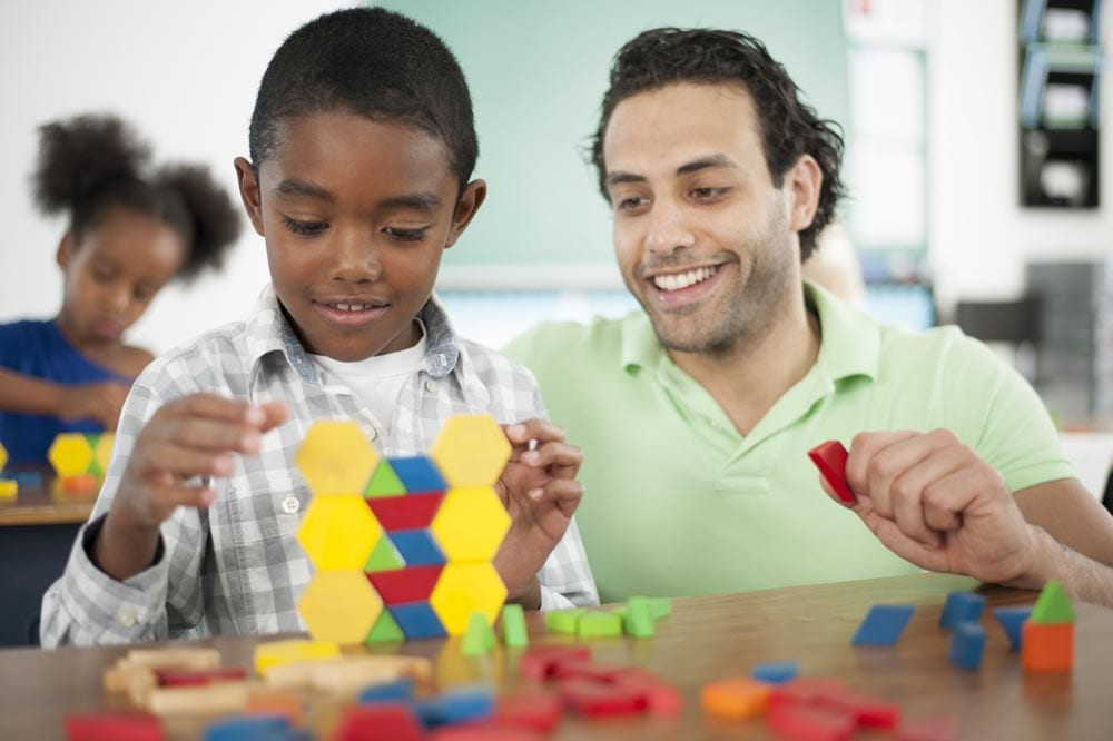 A teacher is helping a student with stacking blocks in class.