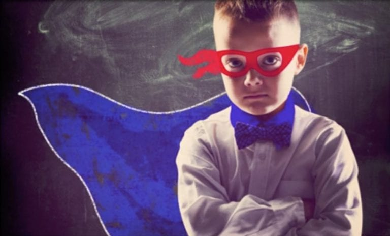 child in super hero costume with a blue cape and red mask in front of a dusty chalkboard