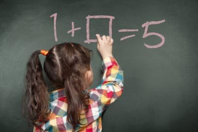 Young girl doing mathematical problems on the blackboard