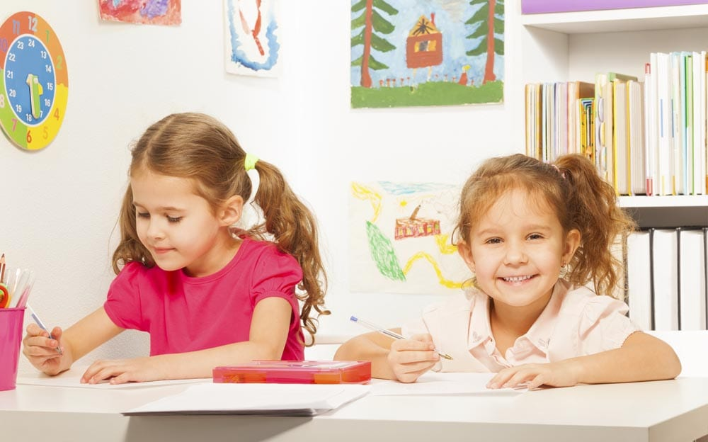 Two clever schoolgirls writing with the pen at the copybook in the classroom